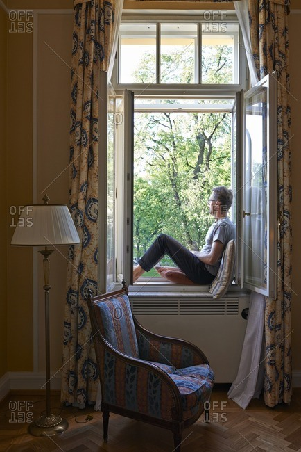 May 23, 2016: Man sitting in a window seat and looking out of an open window