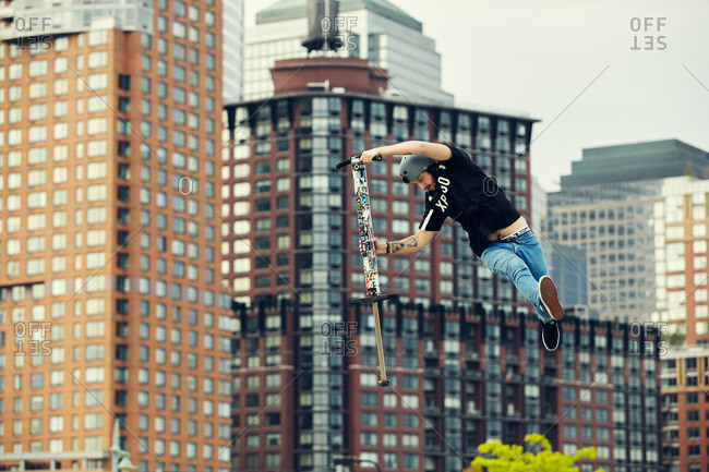 Manhattan, New York City, NY - May 21, 2016: Young man doing tricks in mid-air with a pogo stick