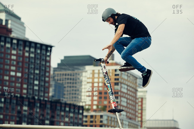 Manhattan, New York City, NY - May 21, 2016: Young man performing tricks in mid-air with a pogo stick