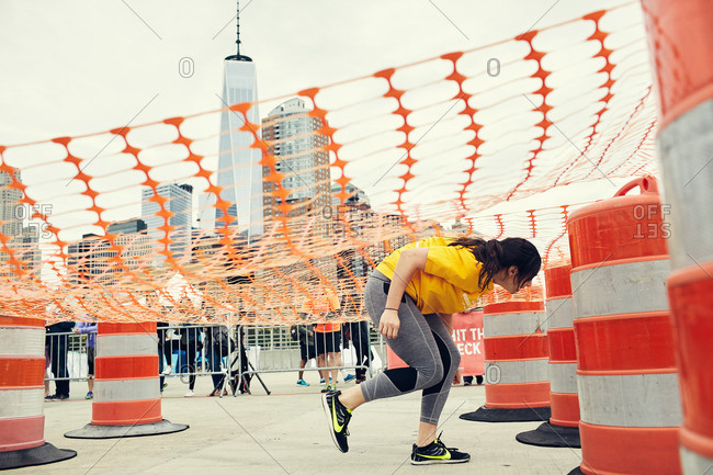 Manhattan, New York City, NY - May 21, 2016: Young woman ducking under an orange net on an obstacle course