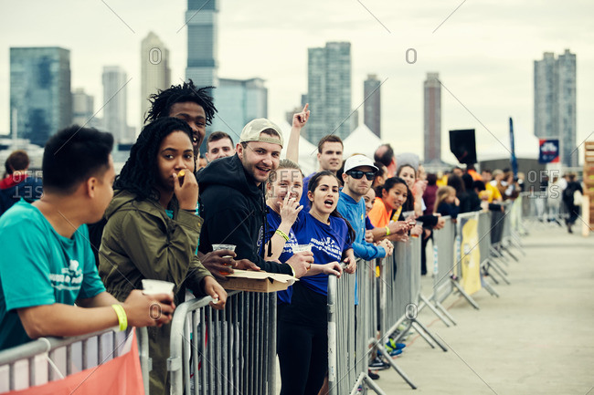 Manhattan, New York City, NY - May 21, 2016: Crowd standing behind fence cheering on competitors