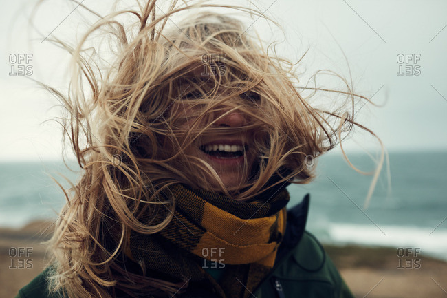 Blonde woman with wind-blown hair on a beach, Montauk, New York
