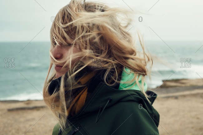 Side view of a woman with wind-blown hair on a beach, Montauk, New York