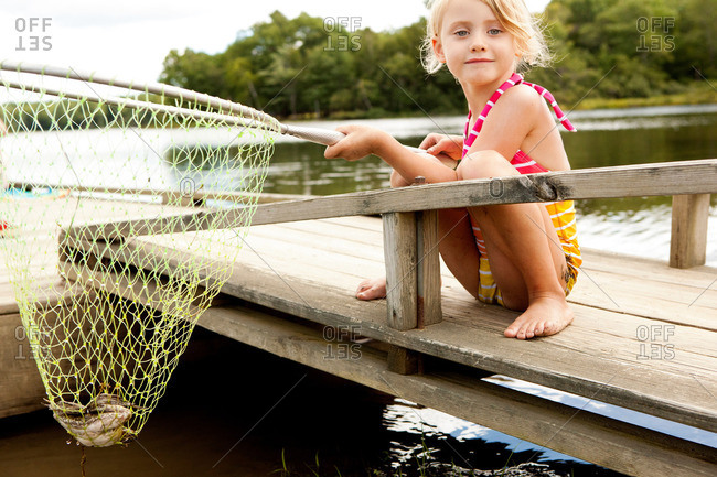 Girl on jetty with frog in fishing net