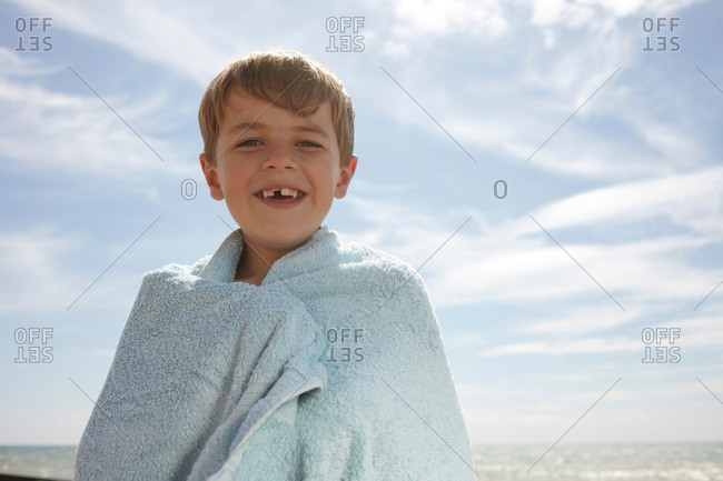 Boy by the sea, wrapped in a towel