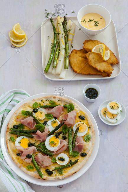 Asparagus, ham and egg pizza on a table