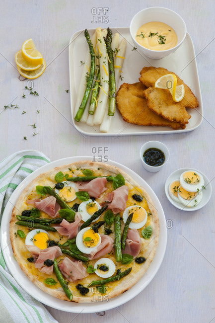 Overhead view of an asparagus, ham and egg pizza