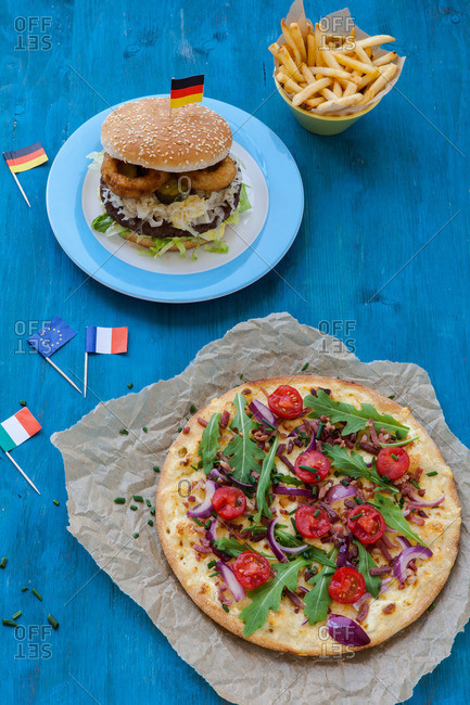 Hamburger and pizza with small Italian and German flags on a table