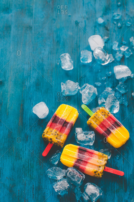 Popsicles and ice cubes on a blue table