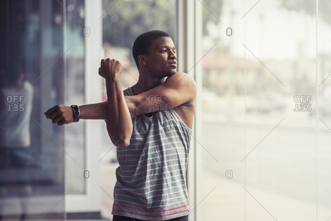 Athletic man stretching his arms before workout