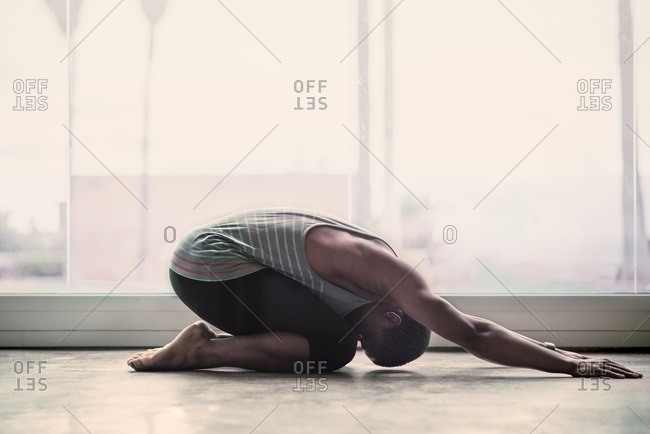 Male ballet dancer stretching in a studio