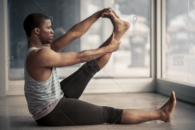 Male ballet dancer stretching his calves in a studio
