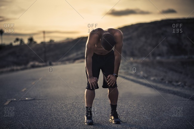 Athletic man taking a breather during a run