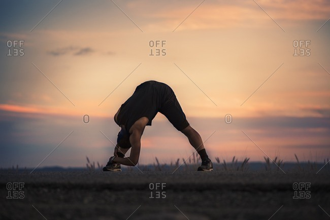 Athletic man stretching in front of colorful sunset
