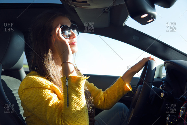 Portrait of a young woman driving a car