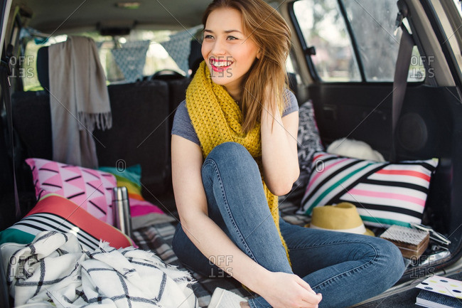Young woman sitting on pillows in the back of an SUV smiling