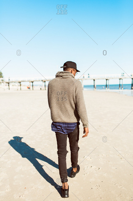 Back view of a young man walking on the beach
