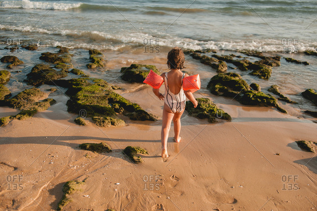 Girl walking on a Portugal beach with arm floaties