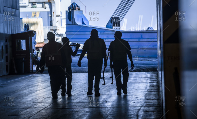 Workers leave a ship after unlashing cargo