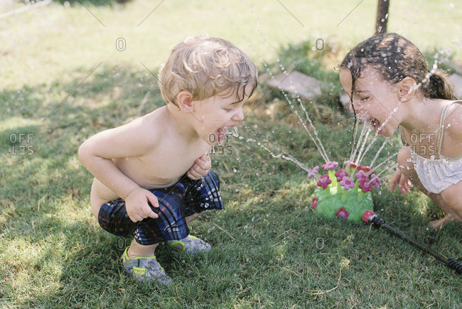 Two children drinking from a sprinkler
