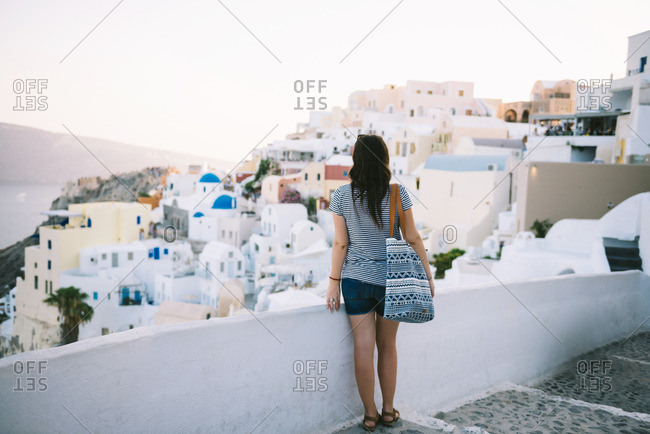 Greece- Santorini- Oia- back view of  woman looking to the village at evening twilight