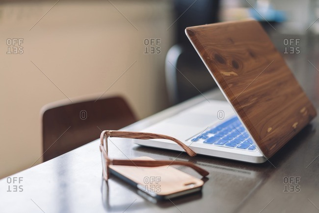 Wooden laptop- smartphone and glasses on desk
