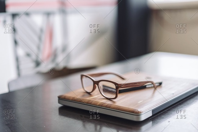 Wooden laptop and wooden glasses on desk
