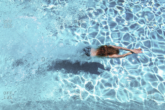 Woman diving underwater in swimming pool