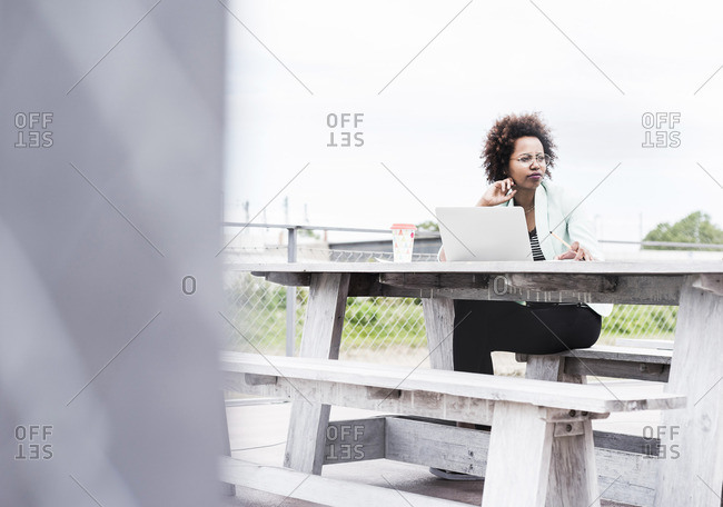 Pensive businesswoman working outside with her laptop