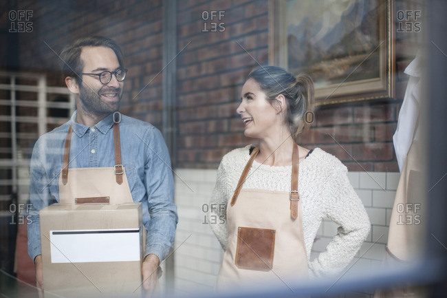 Two smiling colleagues with cardboard box