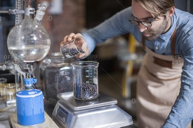 Man weighing ingredients in distillery