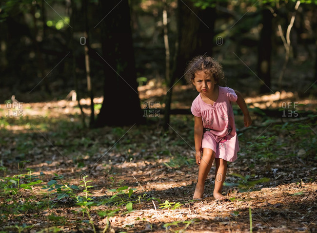 Little girl standing in forest scratching bite from mosquito
