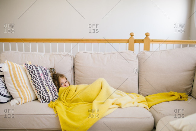 Sick little girl resting on a couch with yellow blanket
