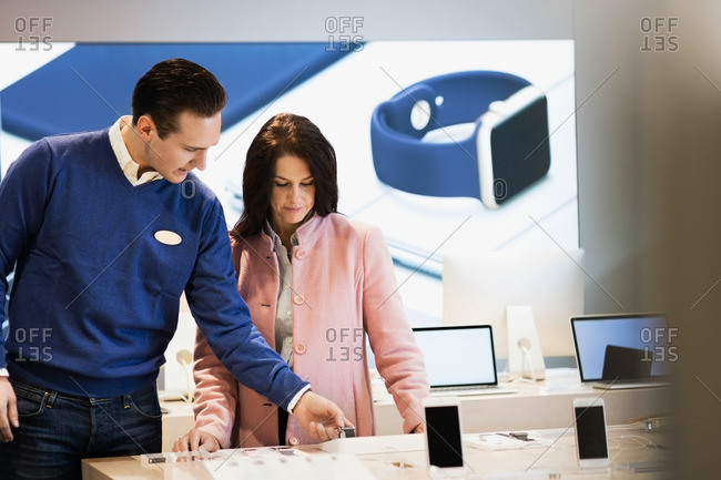 Salesman assisting customer in buying smart watch at store