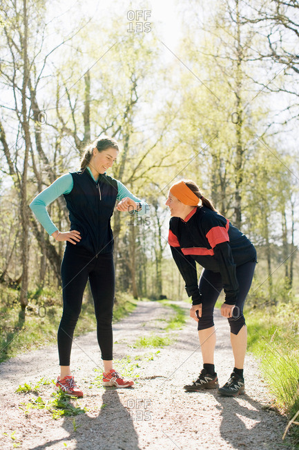 Woman checking time with sister after jogging