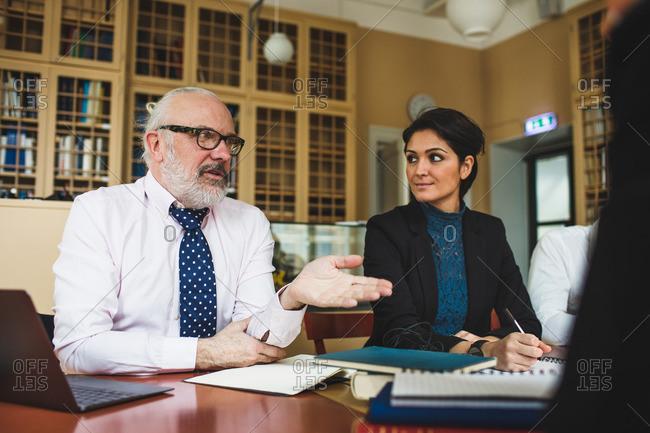 Senior lawyer discussing with coworkers during meeting in library