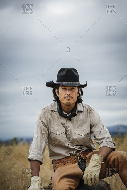 Portrait of a cowboy wearing hat and leather chaps