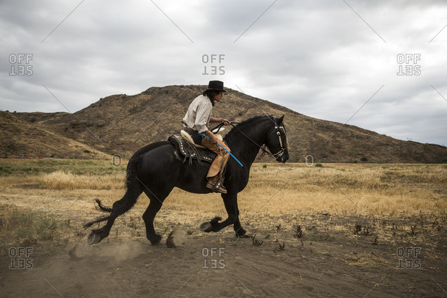 Cowboy riding his horse in dusty field near hills
