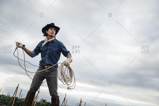 Low angle view of cowboy swinging a lasso rope