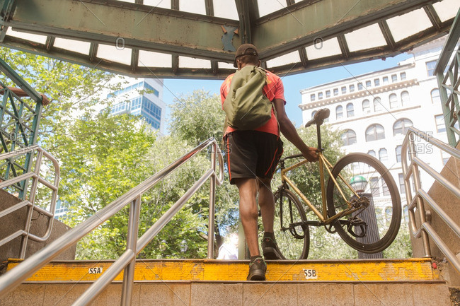 Man carrying bicycle up subway steps, New York