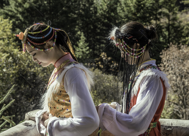 Jiuzhaigou, Sichuan, China - October 21, 2014: Young woman helps her friend tie costume