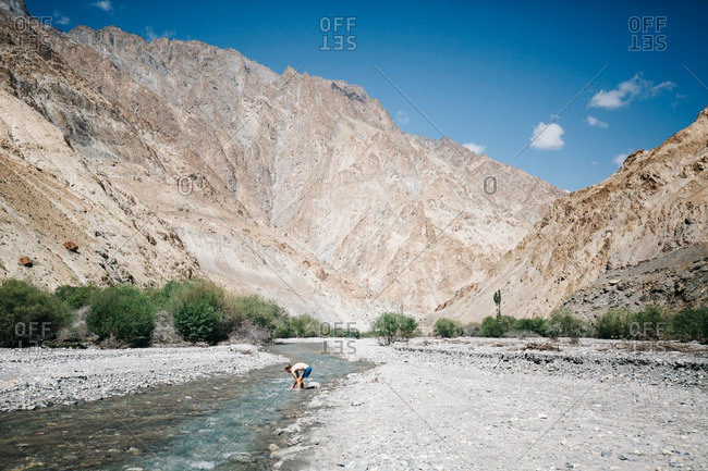 Ladakh, India - June 3, 2016: Man washing his hands at a shallow river in a mountain valley