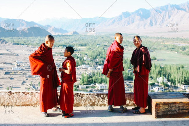 Ladakh, India - June 13, 2016: Young monks standing near a wall overlooking a vast valley
