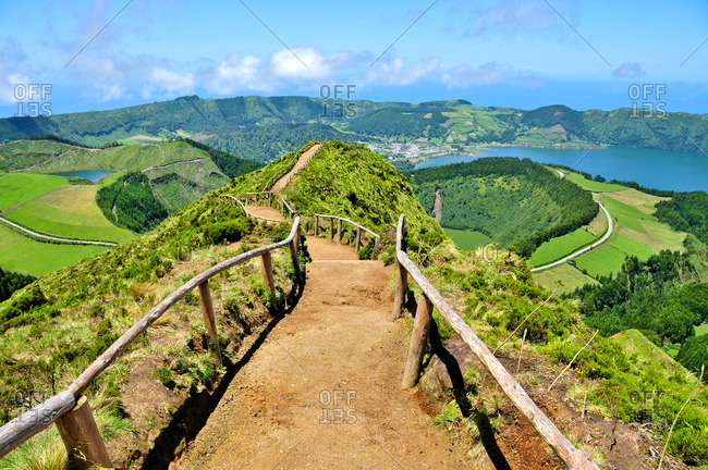 Hiking path with wooden railing on a mountain top ridge