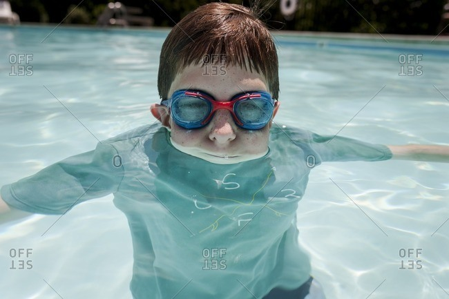 Boy floating in a swimming pool