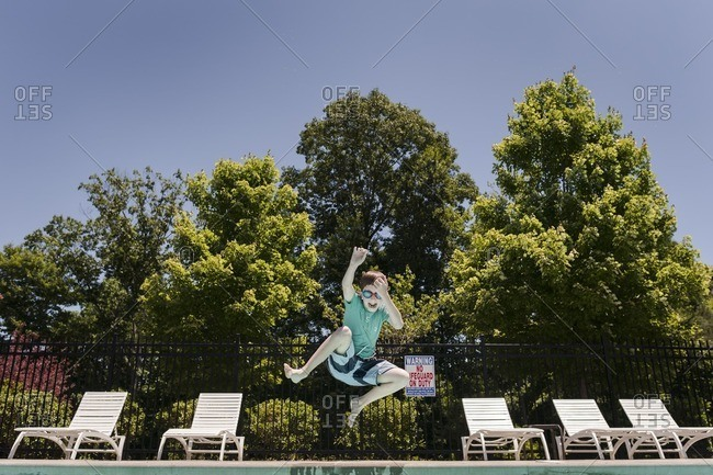Boy leaping into a swimming pool