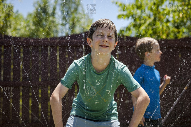 Boy getting sprayed with sprinkler