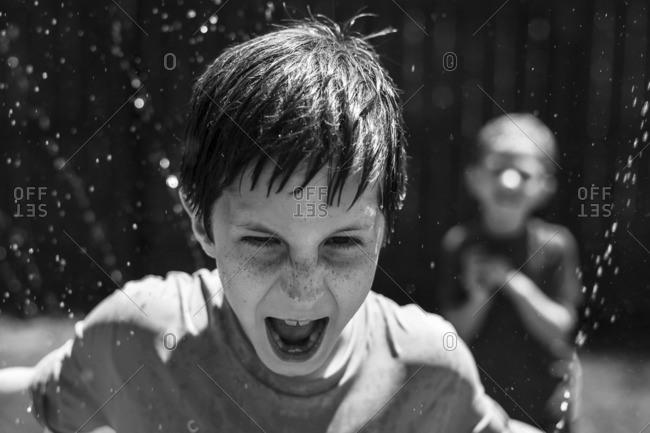Boy with face in sprinkler water