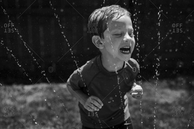 Boy putting his face in sprinkler