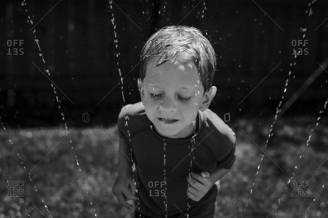 Boy putting face in sprinkler